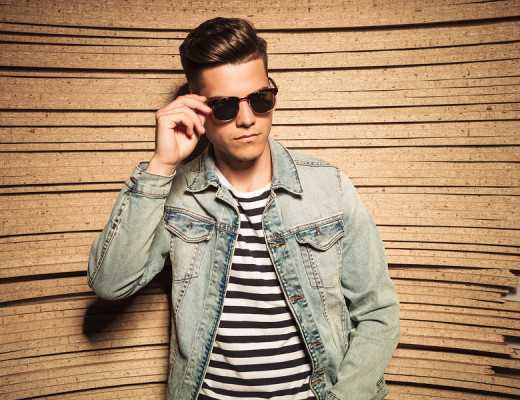 cool young casual man taking off his sunglasses and looks to a his on wooden studio background