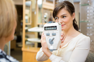 Female optometrist showing pupilometer to mature woman in store