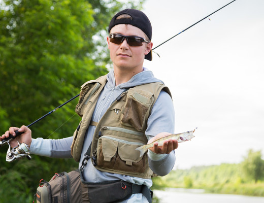 Fisherman in professional gear on the river bank.