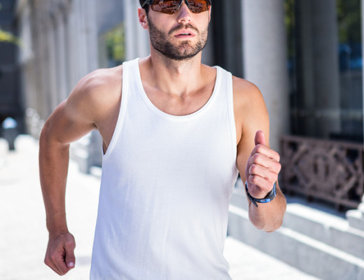 Handsome athlete with sunglasses jogging in the city