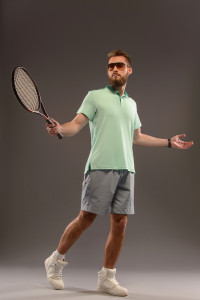 Practicing tennis. Handsome young man holding tennis racket and playing tennis while standing isolated on grey background